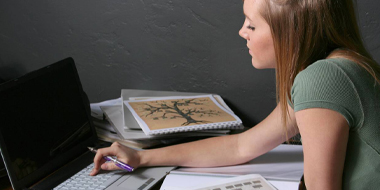 A young woman types on a computer next to documents.